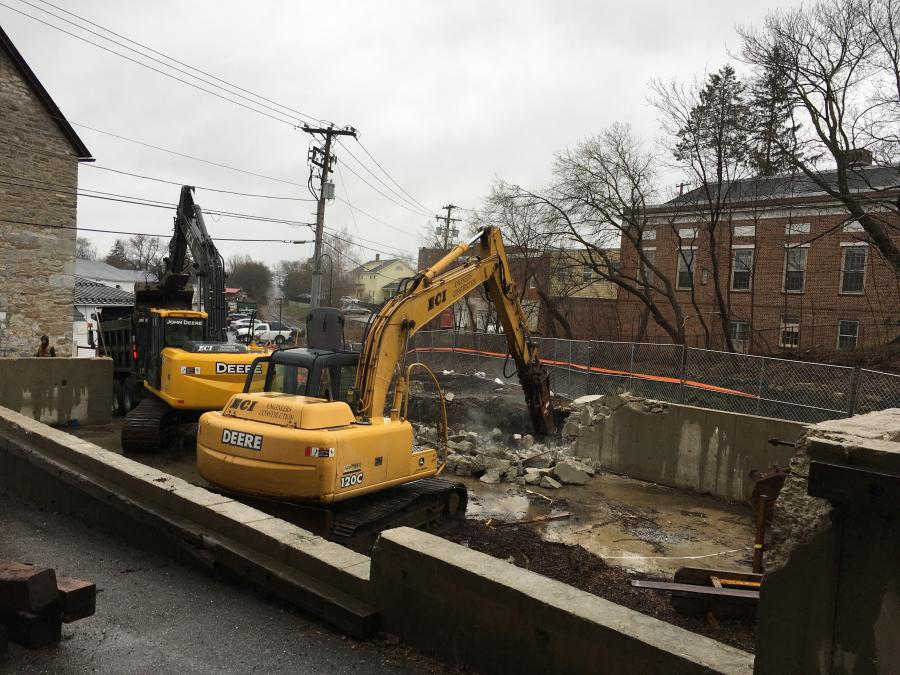 A hammer and loader are demolishing a concrete foundation to prepare for construction of a new drainage system for the downtown rail corridor.