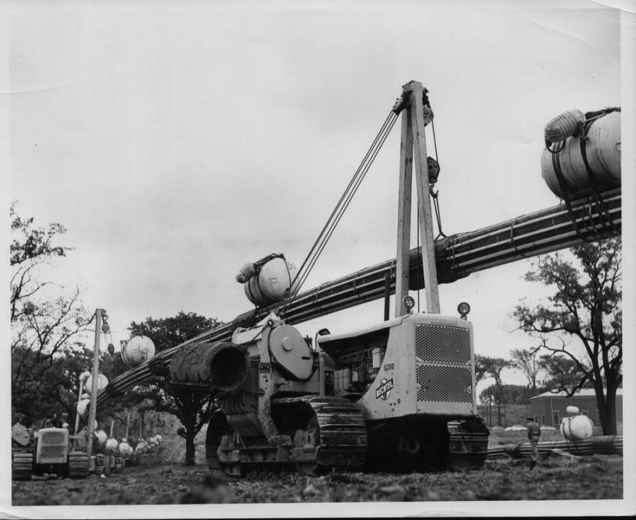 Pipeline construction often required a host of pipelayers to place long sections of pipe. Eight Cat pipelayers are visible in this Sept. 11, 1954 scene as they hold a 600-ft. section of pipe. They will walk it to the edge of the Niagara River during construction of the first pipeline, a natural gas line for the Tennessee Gas Transmission Company, to cross the river. (Dunbar & Sullivan Dredging Company collection, HCEA Archives)