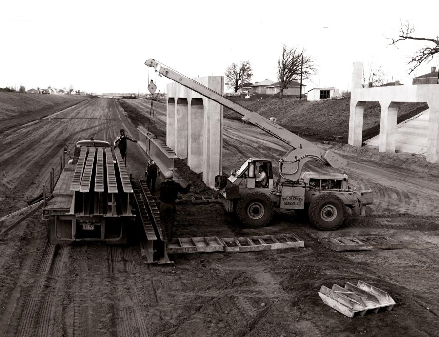 """An Austin-Western hydraulic crane owned by Truck Crane Service Company unloads 32-ft., 1-ton bridge beams during construction of U.S. 65 near Minneapolis, Minn., in 1957. Austin-Western developed the first hydraulic crane, nicknamed the """"Anteater,"""" for military service in World War II, and Grove Manufacturing perfected the industrial hydraulic crane in 1952. (Austin-Western Division of Baldwin-Lima-Hamilton photo, HCEA Archives)"""