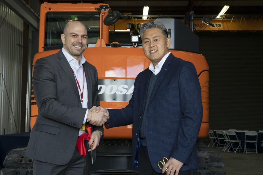 Mike Rye (L), senior vice president at Keen, and Edward Song, president and CEO at Doosan Infracore North America LLC, celebrate the partnership between the two companies with a ribbon-cutting ceremony on Jan. 21, 2020.