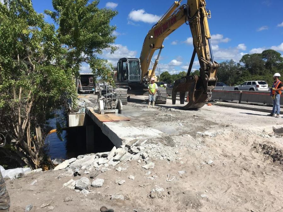A Komatsu 450 excavator picking an existing concrete deck slab and performing demo on the existing I-95/Hillsboro Canal bridge, separating Palm Beach County on the north and Broward County to the south.