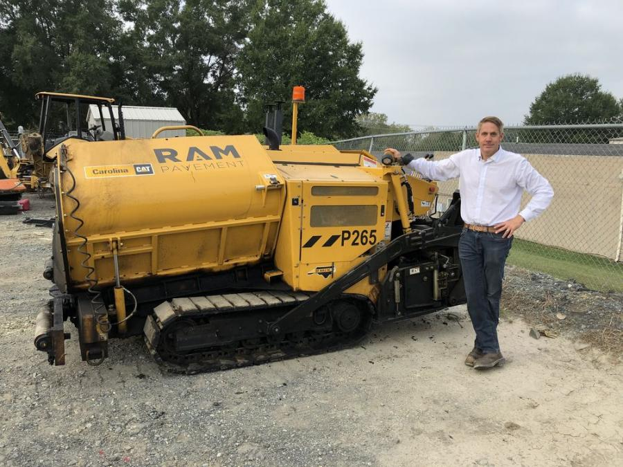 RAM Pavement President Rob Miller poses with a Weiler P265 commercial paver sold to him by Carolina Cat.