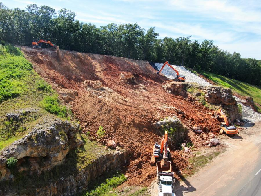 A lane drop helped dump trucks pull off to the roadside site before backing in at an angle onto a specially built pad. From there, materials were loaded and unloaded as excavators navigated the 8-ft. embankments above.