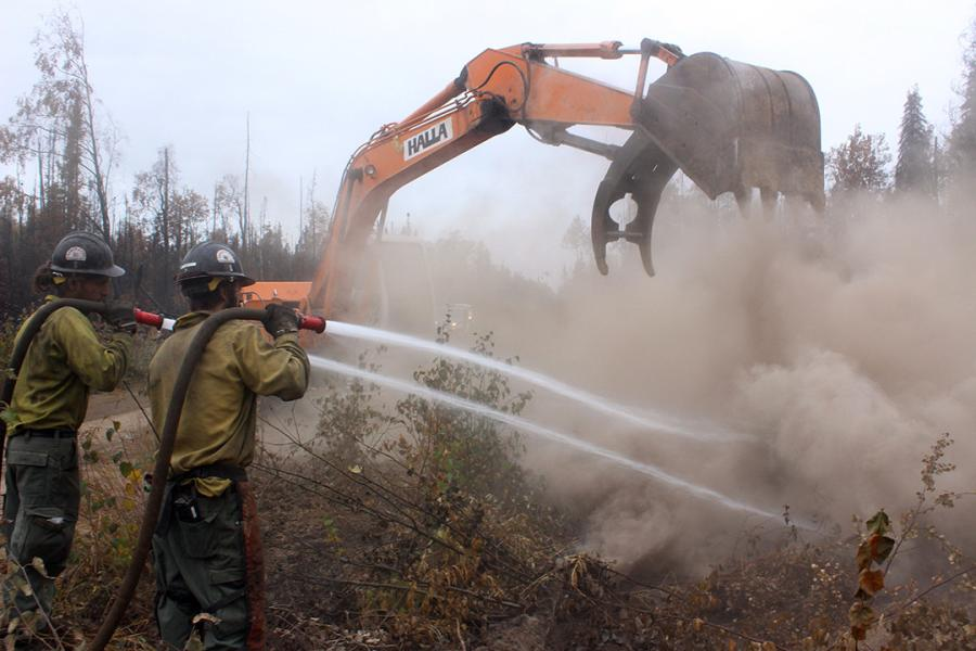 With the help of an excavator, crews on the ground fight wildfires in Alaska.