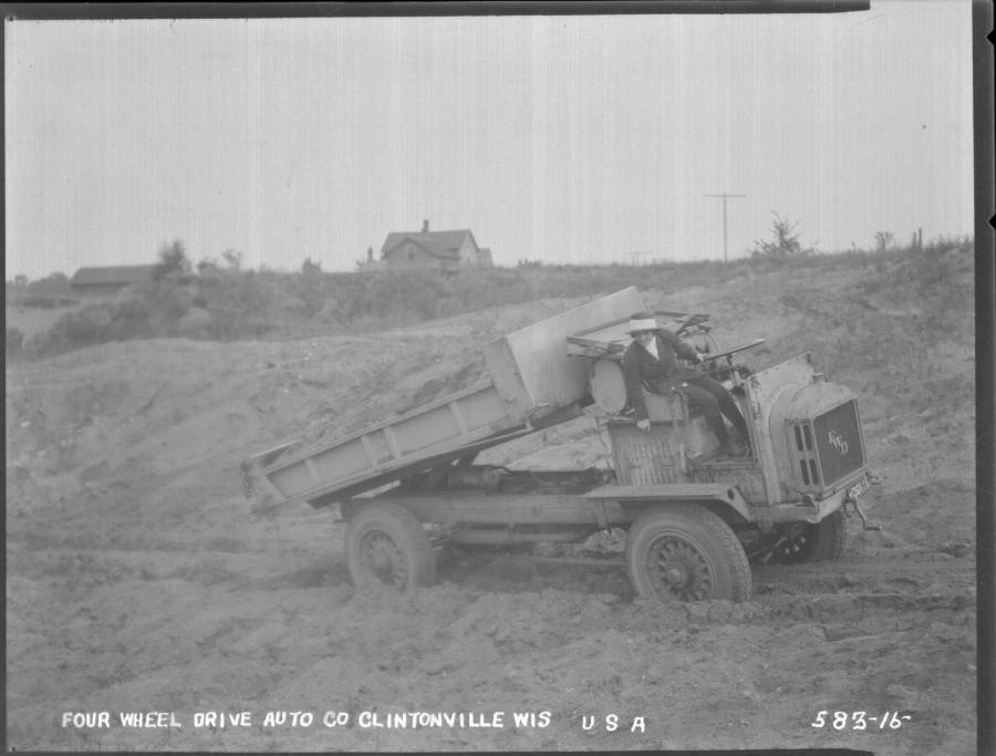 Luella Bates — driving a Model B FWD truck — unloading sand.
