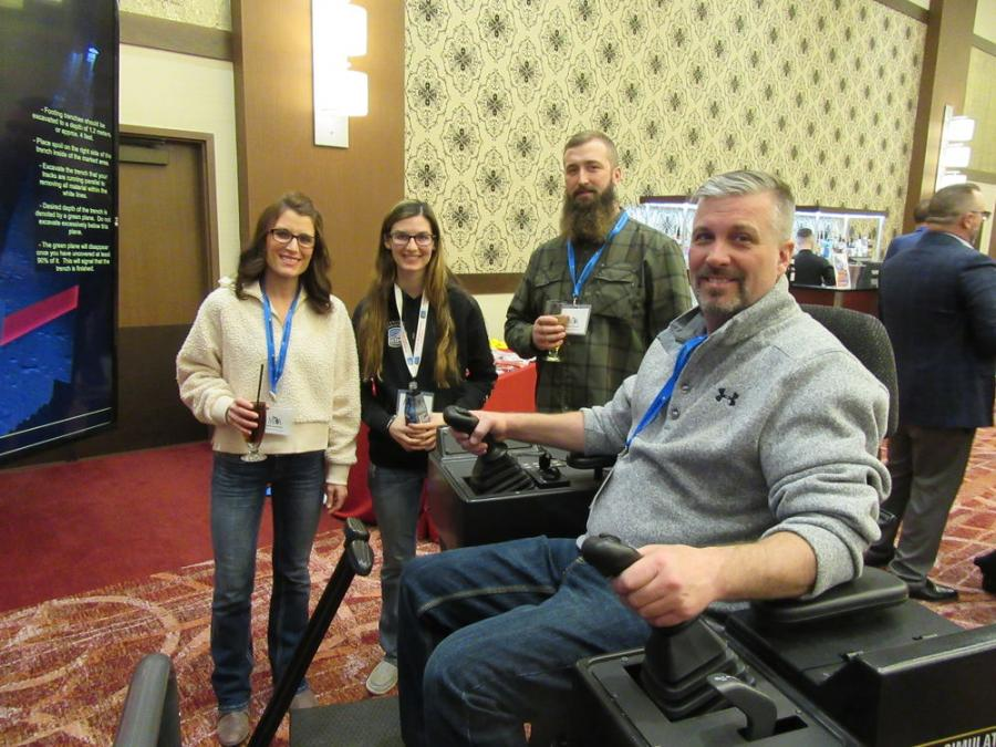 (L-R): Kelly Kominek of Stoneco of Michigan; Danielle Athey of Operating Engineers Local 324; and David Stranyak of Stoneco of Michigan watch as Kelly's husband, Larry Kominek of Stoneco of Michigan, tries his hand at a simulator during the event.