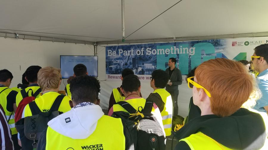 Josh Patnode, representing Lift & Move USA, tells students from Clark County School District about the role of specialized transportation, rigging, and lifting in building Allegiant Stadium at the Workforce Solutions area during ConExpo-Con/AGG.