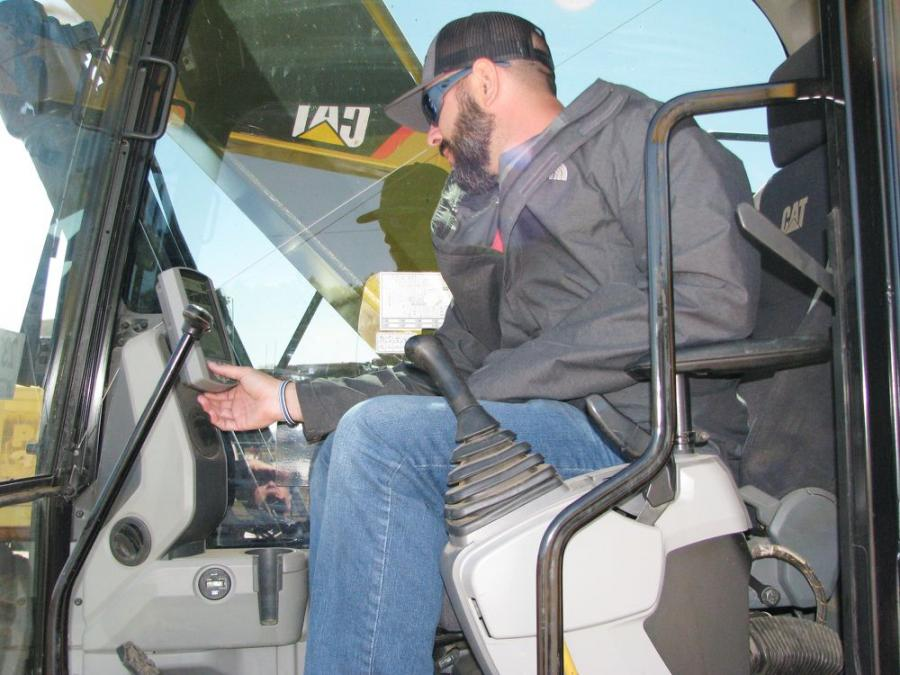 Getting acclimated to the touch screen display of a Caterpillar 326FL is Tommy Krumland, an independent equipment dealer based in Kansas City, Kan.