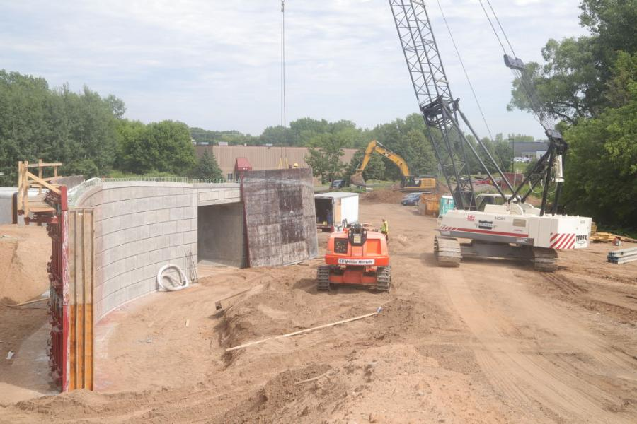 To give a pictorial perspective on the 350,000 cu. yds. of fill dumped on the TH36/Hadley interchange rebuild, the top of this 100-ft. culvert now carries Hadley Avenue over the Gateway Trail. The boom of a Terex crane looms over the tunnel while a Cat excavator in the far background excavates for new storm sewer.