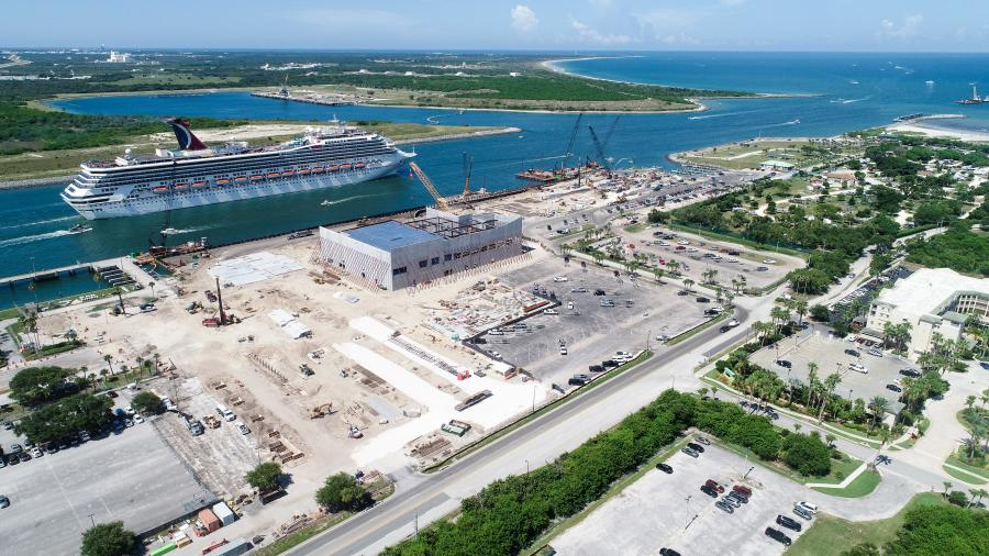 The Carnival Liberty sails past construction of the cruise line's newest home at Port Canaveral in Florida.