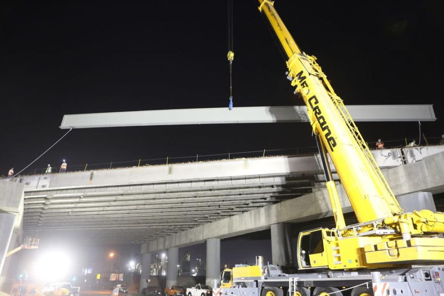 Here, a beam is about to be placed on a new bridge. Night work was essential on the busy freeway.