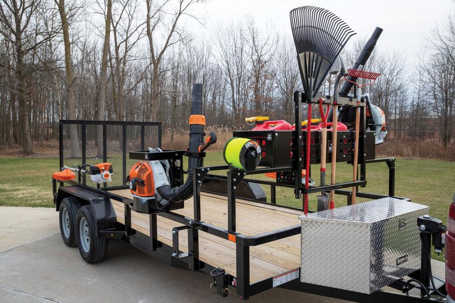 """An """"all-in-one"""" storage solution leaves the floor below it open for riding mowers. It includes a basket with space for gas cans and loose items, a rack for blowers, a trimmer line holder and an optional rack for hand tools."""