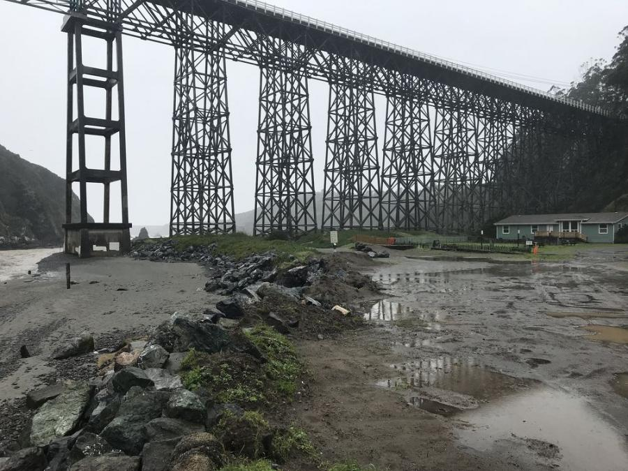 The Albion River Bridge's existing structure constructed with Douglas fir timber is vulnerable to seismic events and takes up a significant footprint on the beach with its timber towers.