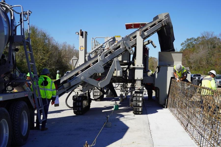 The Power Curber 7700 is a paving machine that forms concrete into a barrier rail. The concrete is extruded from the truck, travels up the conveyor belt and into the chute, where it is formed into the rail.