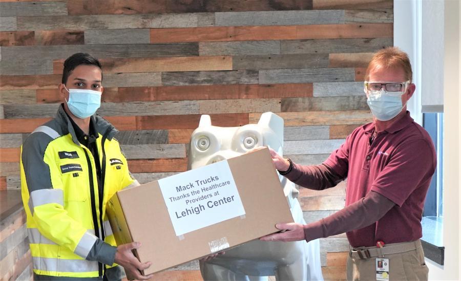 LVO employee Richi Ramlal (L) presents face shields to Lehigh Center representative Glenn Trunk.