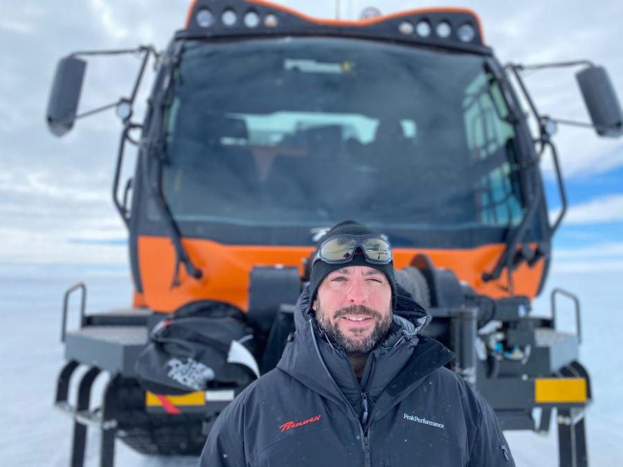 Prinoth's Director of Engineering at the North American office Eric Steben stands in front of Panther vehicle in Antarctica.