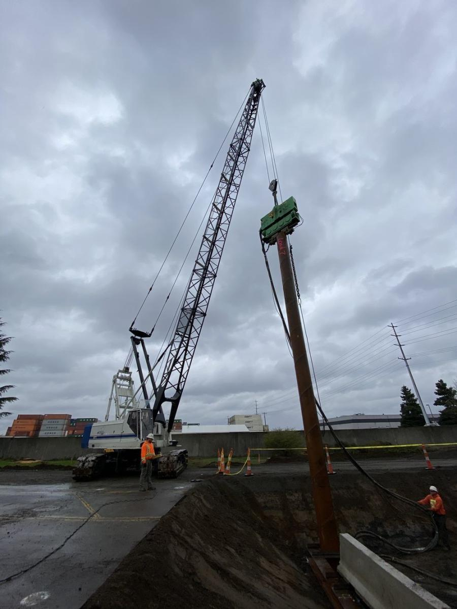 Workers from Cascade Bridge install initial section of piling using vibratory pile hammer.