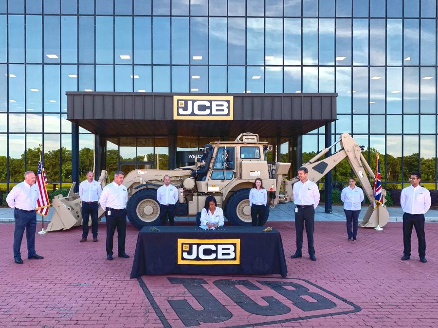 JCB North America President and CEO Richard Fox-Marrs (R) and JCB Vice President of Government and Defense (L), along with the JCB Government and Defense team, look on as Viengkeo Johnson, contracts manager of JCB, signs the new contract to produce a fleet of specialized high-speed excavators over the next eight years for the U.S. military in a deal worth up to $269 million.