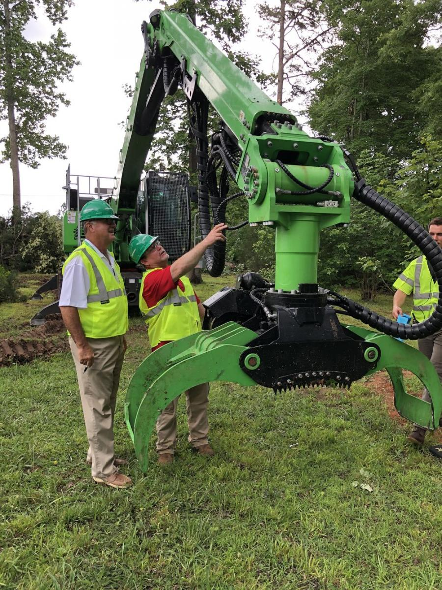 Sam Caldwell (L) of Sun Machinery in Lexington, S.C., and Brian Ligon of Big Dog Tree Service in Augusta, Ga., look over the grapple attachment on the Sennebogen 718E.
