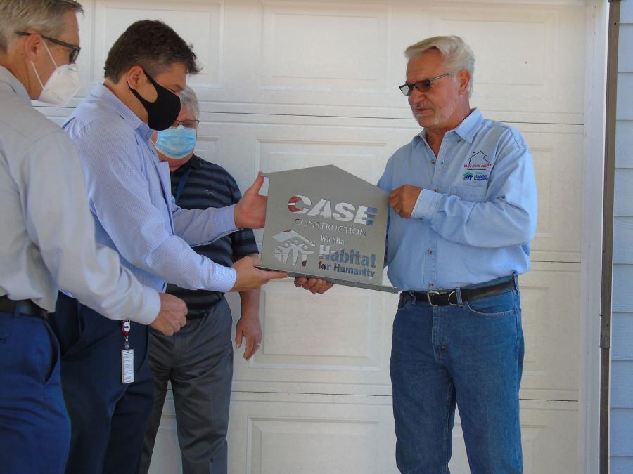 Bill Bauck, Wichita Habitat for Humanity board member, presents a plaque to Case.