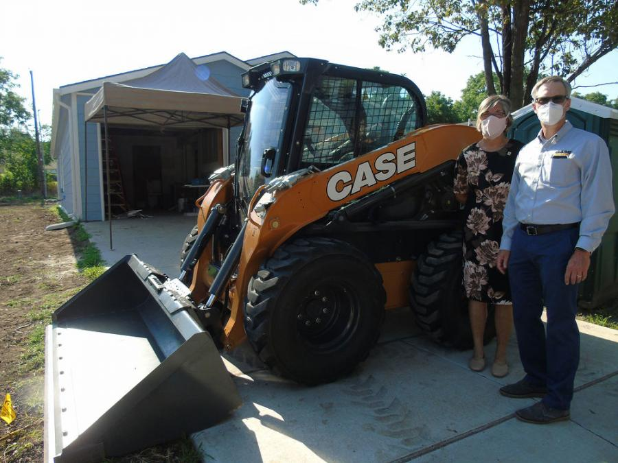 Ann Fox of Habitat and Troy Williams of Case stand next to the donated skid steer.