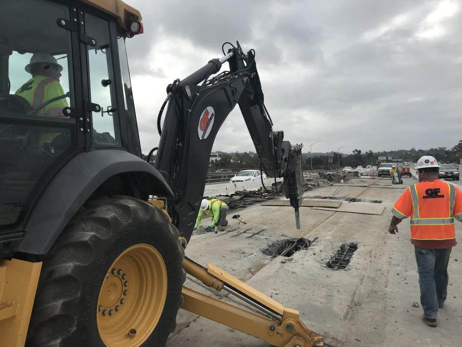 A John Deere 710 backhoe with a hydraulic breaker is demolishing a section of a concrete bridge deck as part of the $25.7 million project in Chula Vista, Calif.