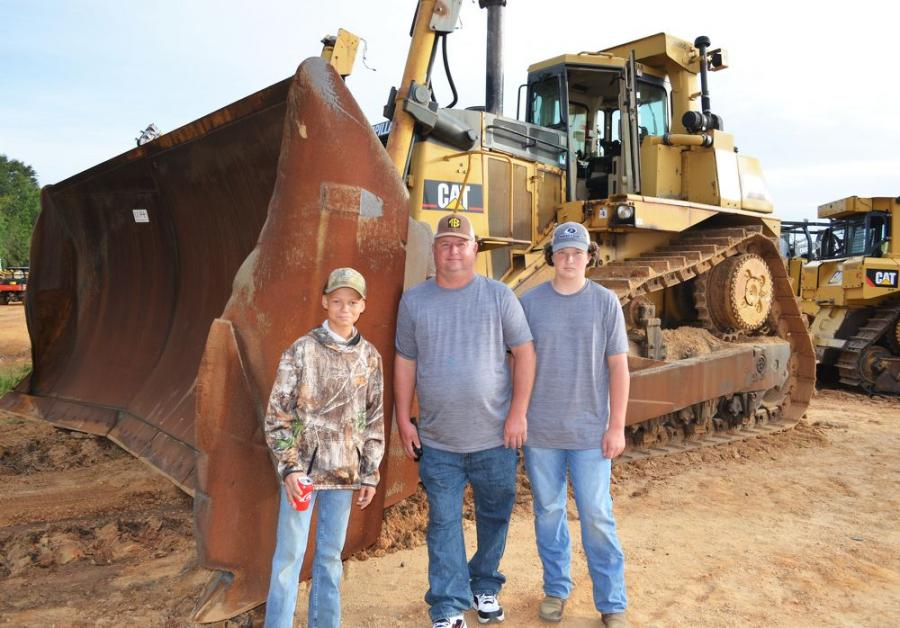Admiring the size of the big Cat D10R in the auction are (L-R): Nicholas Grigsby, David Bradley and Easton Bradley of Bradley Excavation, Killen, Ala.