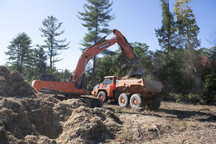 After processing the trees into mulch, another excavator loaded it in an articulated dump truck (ADT). The truck traversed the rough terrain to deliver the mulch to assigned areas. There, the employees placed the mulch for erosion control purposes.