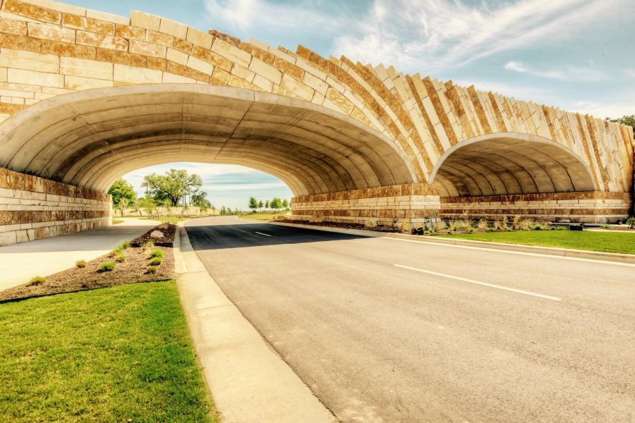 Kissing Tree Bridge — Iconic bridge that is the entrance to Kissing Tree, which is a community in San Marcos. Veneer limestone quarry blocks were used on the exterior. (WLE photo)