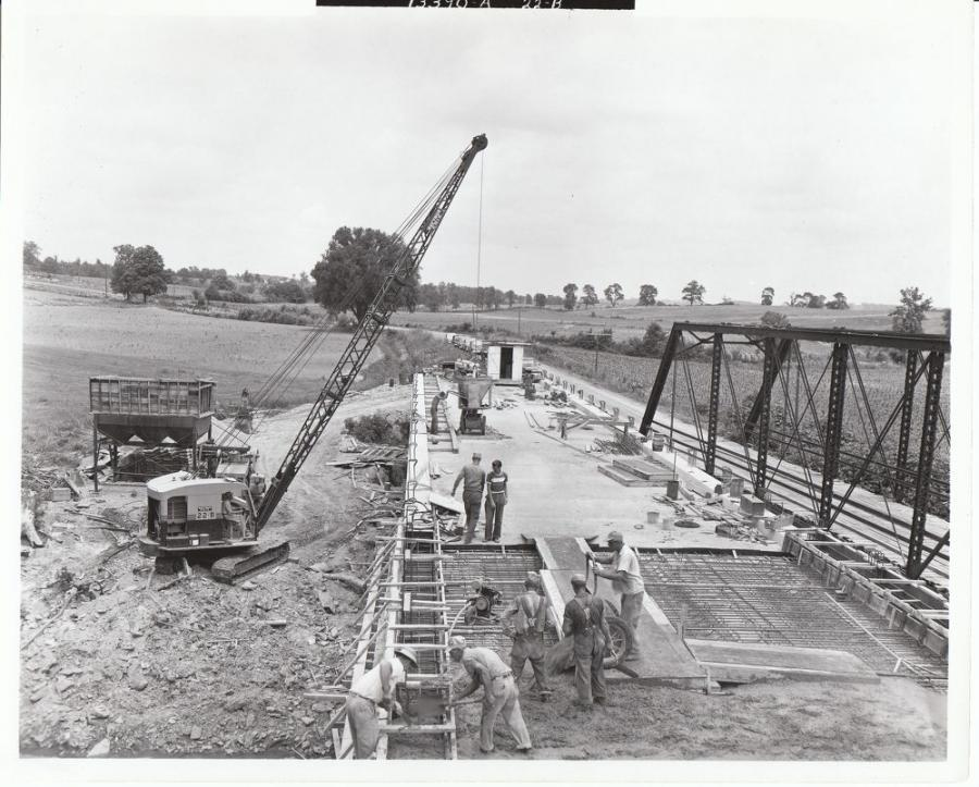 Construction of a small bridge, with a Bucyrus-Erie 22B crawler crane loading concrete into a hand cart for delivery. The small batch plant provides the concrete; the mixer – possibly a small dry batch paver – is behind the crane. Laborers are shoveling concrete into the curb area where the cart can't go, and the power unit for a vibrator sits on the rebar behind them. 
