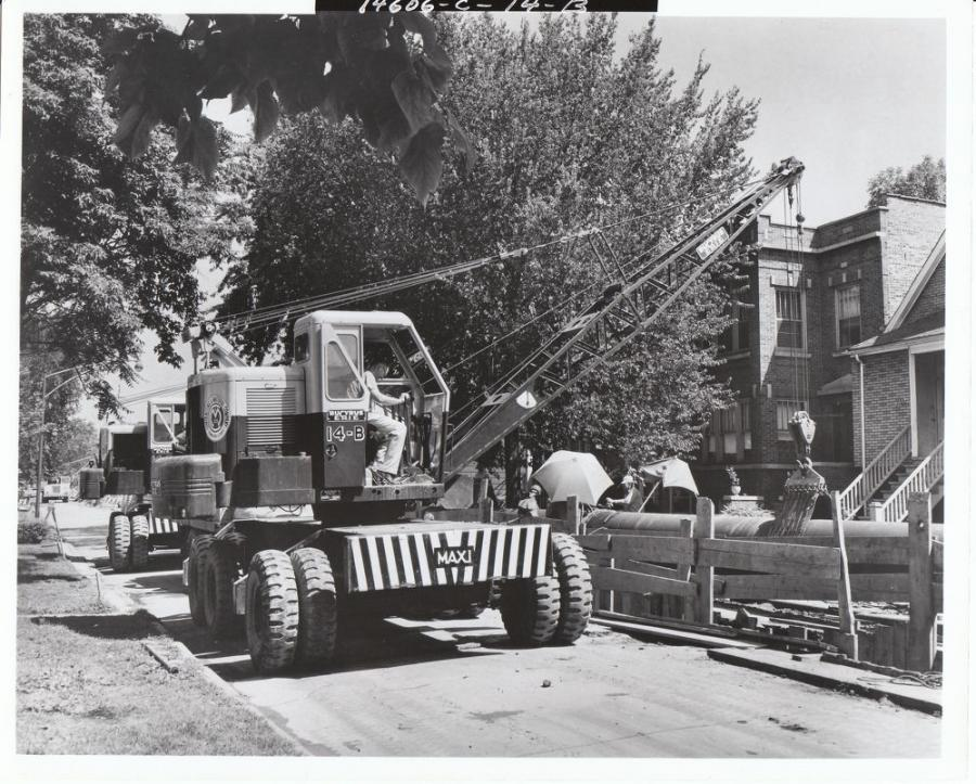 "Contracting & Material Company of Evanston, Ill., has a pair of Bucyrus-Erie 14B cranes setting pipe on a residential project. These 15-ton capacity cranes, which B-E called wagon cranes although they were self-propelled,  ride on model 4215 carriers built by Maxi Corporation. Maxi was formerly Six Wheels Inc.; the Maxi name originated with the Six Wheels advertising slogan of ""Maxi Engineering."" 