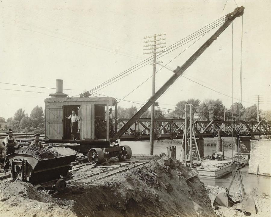 A Type B traction crane, one of six Eries (four cranes and two shovels, in the years before convertible excavators) owned by contractor T. E. Currie Company, is digging a pier foundation for a highway bridge between Detroit and Mount Clemens, Mich. Note the state-of-the-art hauler, an apparently hand-powered dump car.
