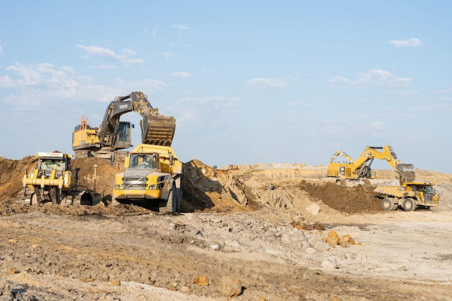 The Volvo EC480E, Volvo A45G, John Deere 950K, Cat 6015B and Cat 775G work to move material to a lower building pad.