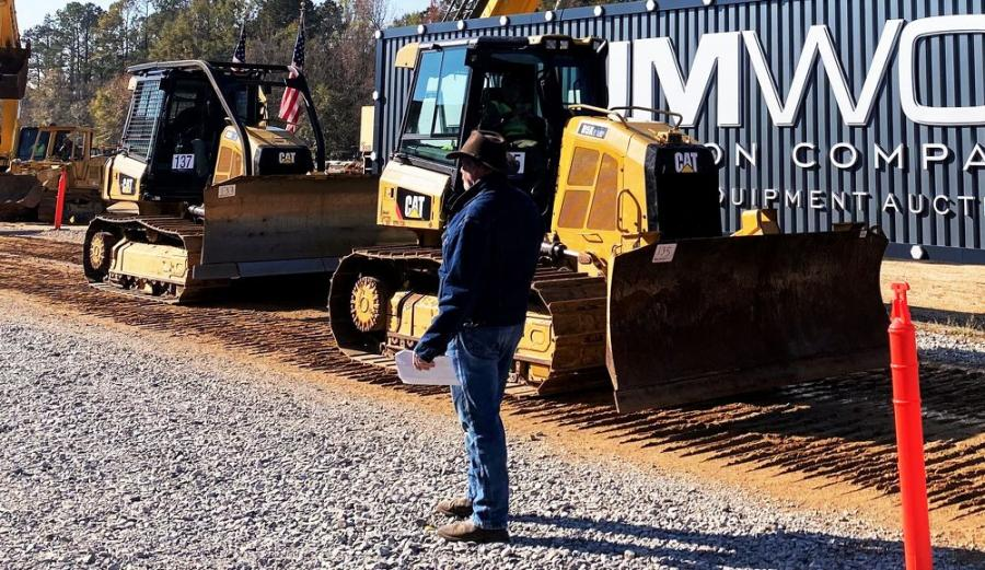 JM Wood staffers usher in an assortment of late-model Cat dozers to be auctioned, including this pair of D5K2s.