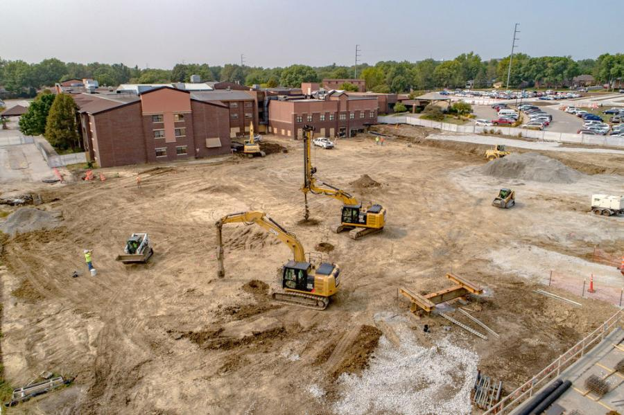 Equipment on site includes excavators; bulldozers for leveling the ground using GPS technology; and side and standard dump trucks.