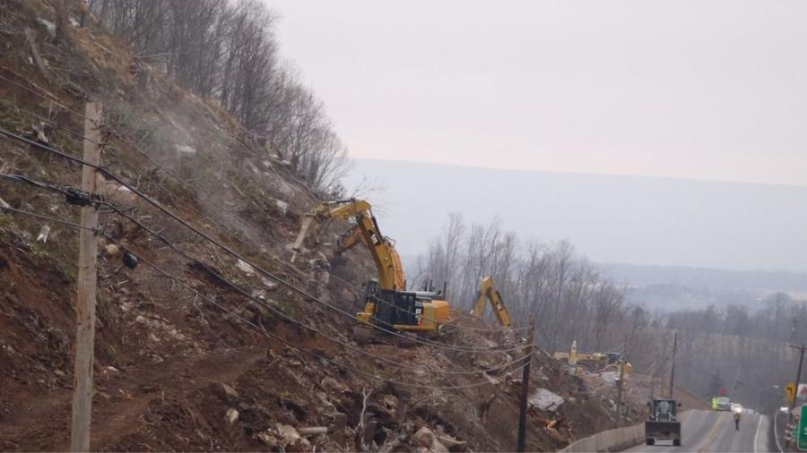 Crews perform boulder removal and slope stabilization prior to excavation in PMG narrow.