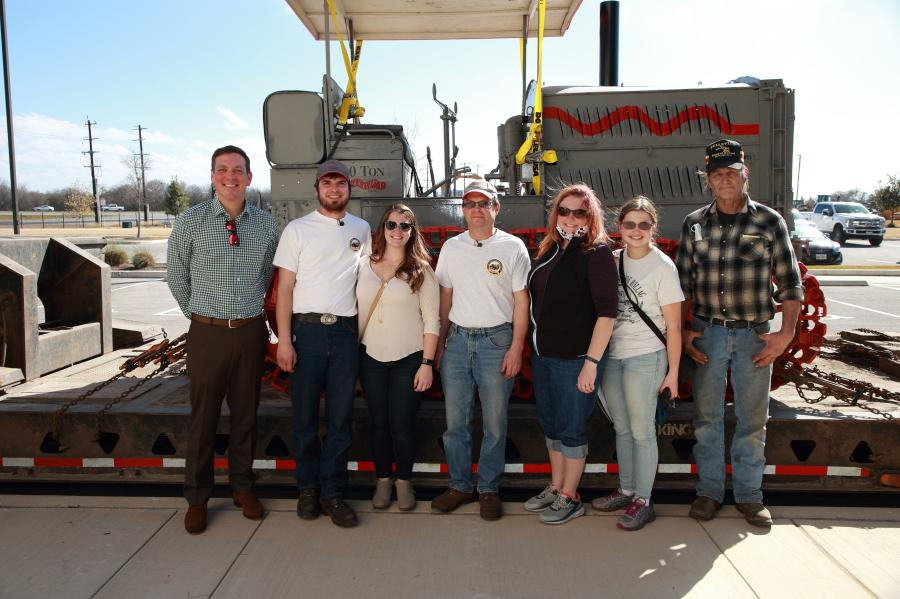 (L-R): Peter J Holt, president/CEO of HOLT CAT; Scott Vouk, and his wife, Kerri Vouk; Tom Vouk; Nancy Vouk; Bonnie Vouk; and Tom the haul driver all pose in front of the Holt 10-ton tractor as it makes its journey home.