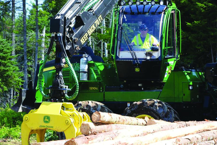 A student in last year's class operates a forwarder loading logs at a felling site.