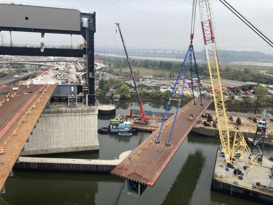 Cranes are playing an essential role in the bridge reconstruction project. Here one lifts a prefabricated deck.