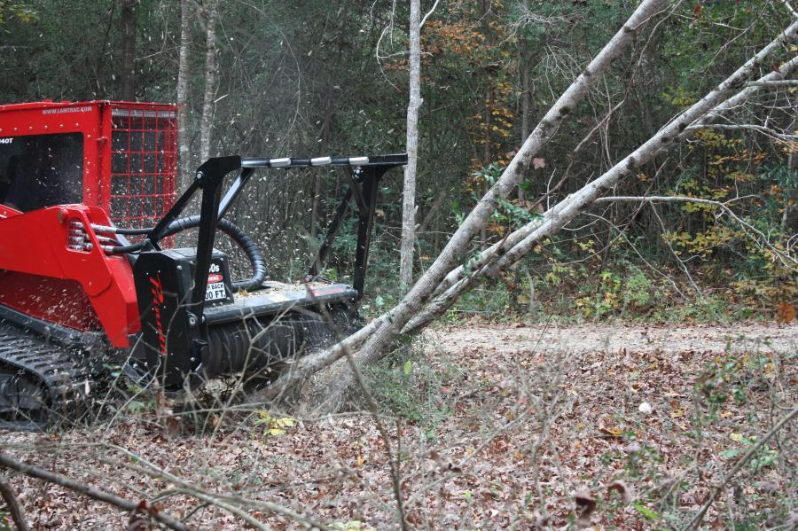 A Prinoth M450e-1900 on a Lamtrac skid steer clearing the edge of the forest.