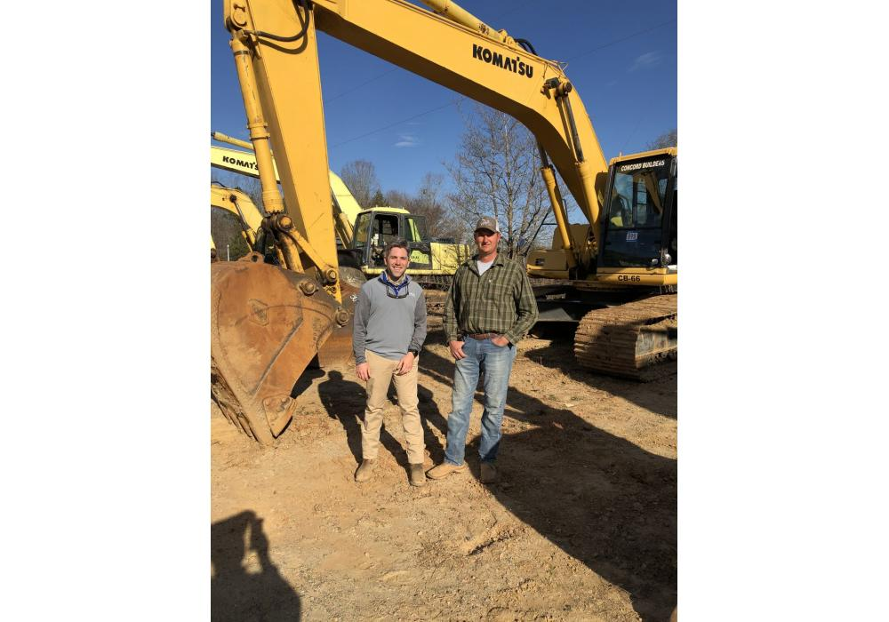 Iron Auction Group's Jared McGaffee (L) welcomes Quentin Deal of Deal Company in Clover, S.C., to the auction. Deal planned to bid on the Komatsu PC 200 excavator.