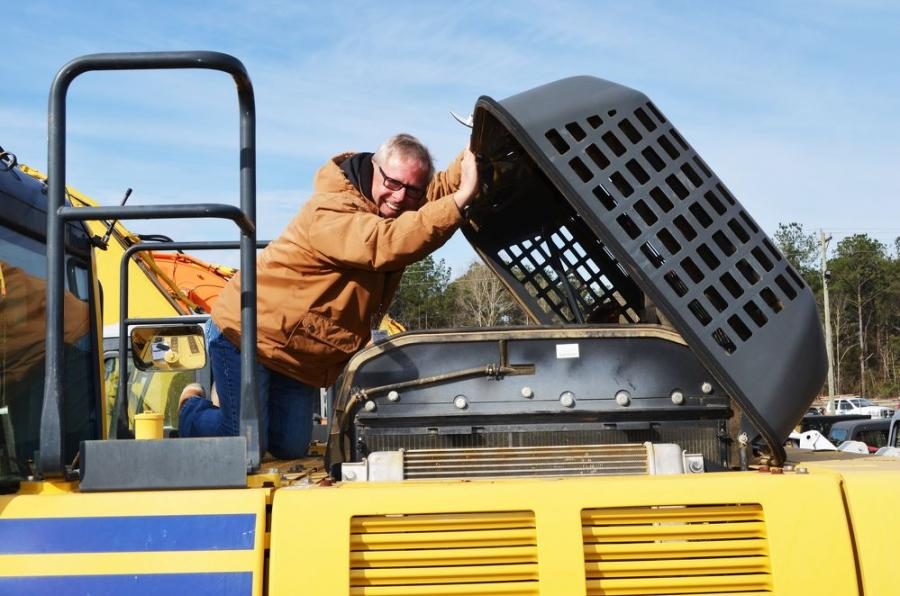 """Tim Spencer of Spencer Ready Mix of Jackson, Miss., does a complete """"stem to stern"""" inspection of this Komatsu PC210LC excavator."""