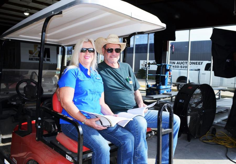 Watching the auction action from the comfort of their golf cart parked inside the auction facility are Tammy Sutton (L) and Dale Rowden of Rowden & Sons, Farmington, Ga.