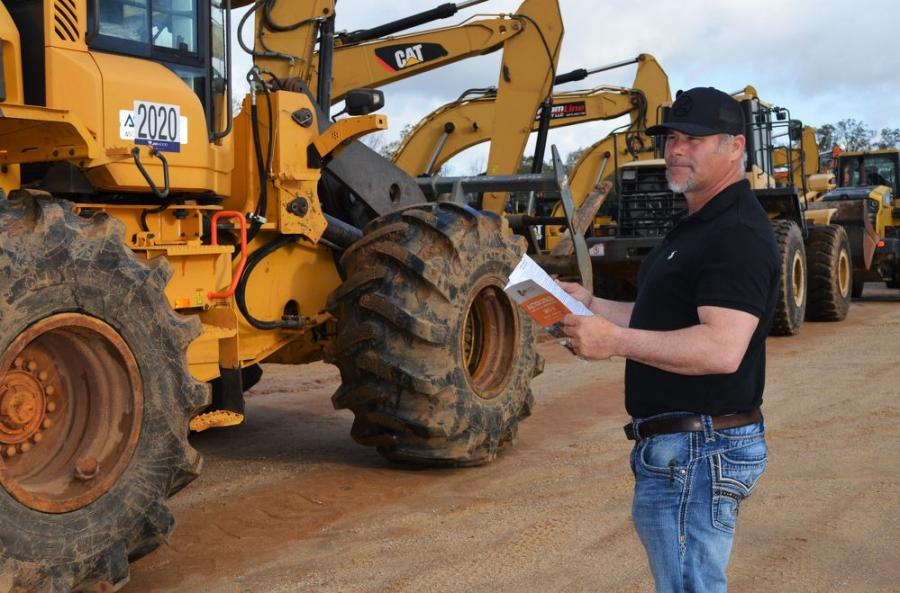 Shawn Carver of Bulldog Trucking & Grading, Appling, Ga., takes one last look at some of the wheel loaders as they slowly roll towards the ramp for auctioning.