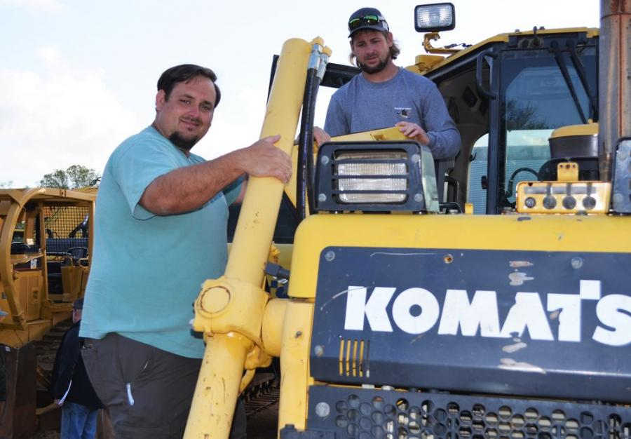Inspecting a Komatsu D65EX dozer are Patrick (L) and Dillon Godwin, independent contractors based in Atmore, Ala.