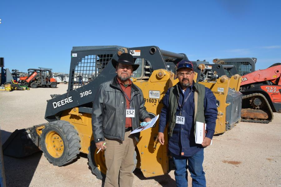Odessa, Texas, buyers Trini Romero (L) and Jose Zunia were meticulous in their inspection of the many skid steers available in Seminole but settled on this Deere 318G. Romero owns TR Welding service and Zunia operates Welding and Fence Construction.