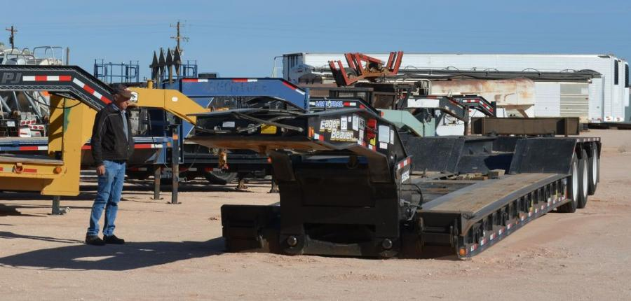 A buyer inspects an Eager Beaver goose neck trailer, one of many trailers up for sale at the auction.