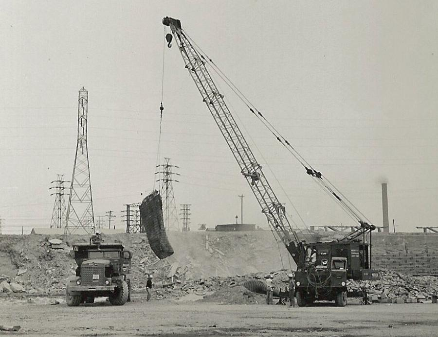 On Aug. 15, 1959, Merritt-Chapman & Scott used a Marion 43-M truck crane to pick a blasting mat during construction of the Niagara Power Project. The hauler is one of approximately 120 R22 and R27 Euclids and PH95 Payhaulers M-C&S massed to handle nearly 17,000,000 yds. of rock excavation on two contracts to construct the power plant, intake structure and two conduits. The mat is placed over a small blast to contain debris. (Marion Power Shovel Company image, HCEA Archives)