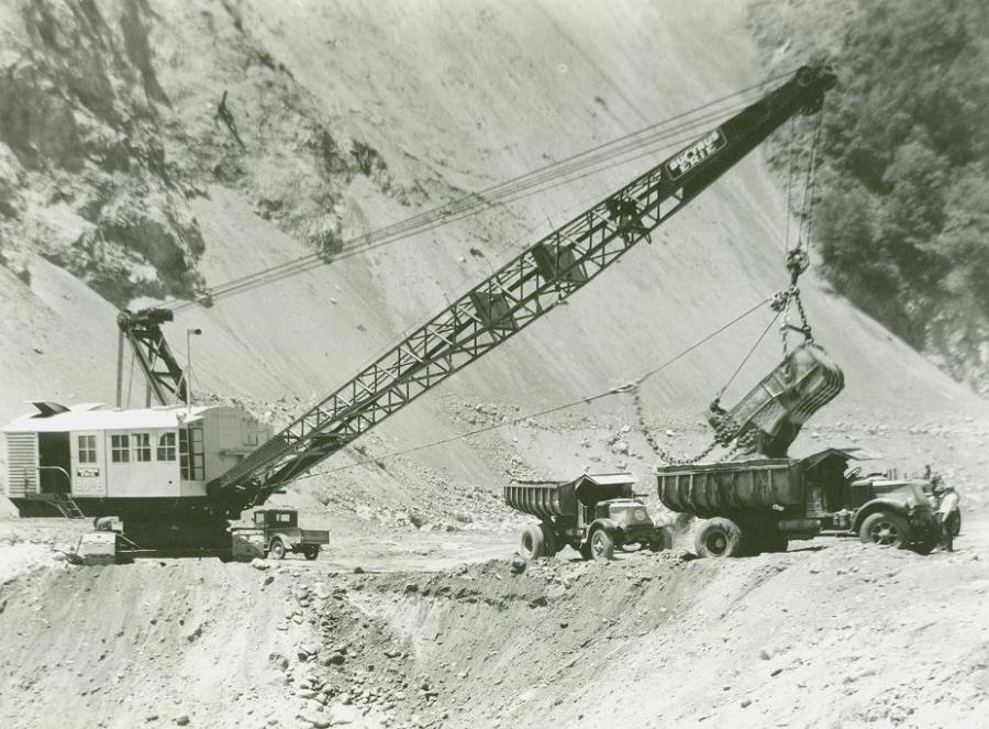 A Bucyrus-Erie 120B electric dragline loads a Mack Super Duty AP truck during construction of San Gabriel Dam north of Azusa, Calif., circa 1933. Built by the West Slope Construction Company joint venture, this was the world's largest rockfill dam when completed in 1937. 