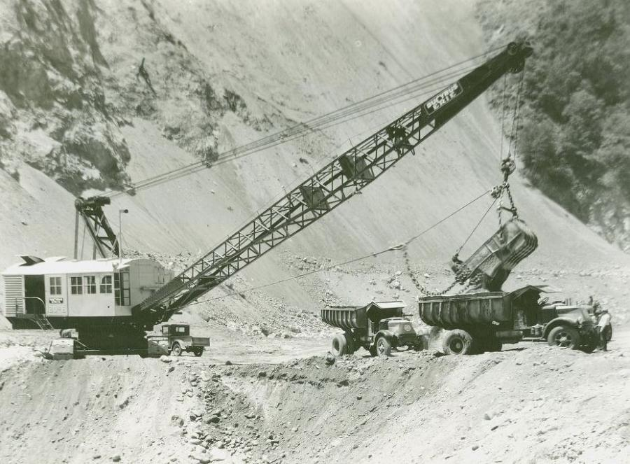 A Bucyrus-Erie 120B electric dragline loads a Mack Super Duty AP truck during construction of San Gabriel Dam north of Azusa, Calif., circa 1933. Built by the West Slope Construction Company joint venture, this was the world's largest rockfill dam when completed in 1937.  (Bucyrus-Erie Company photograph)